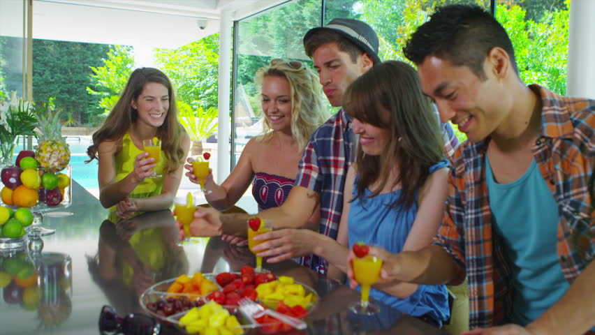 Happy Group Of Friends Drinking Healthy Juice Drinks In Kitchen Modern Home