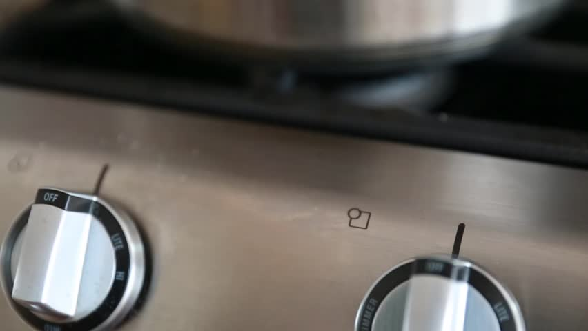 A stainless steel pot on a natural gas stovetop above the flame