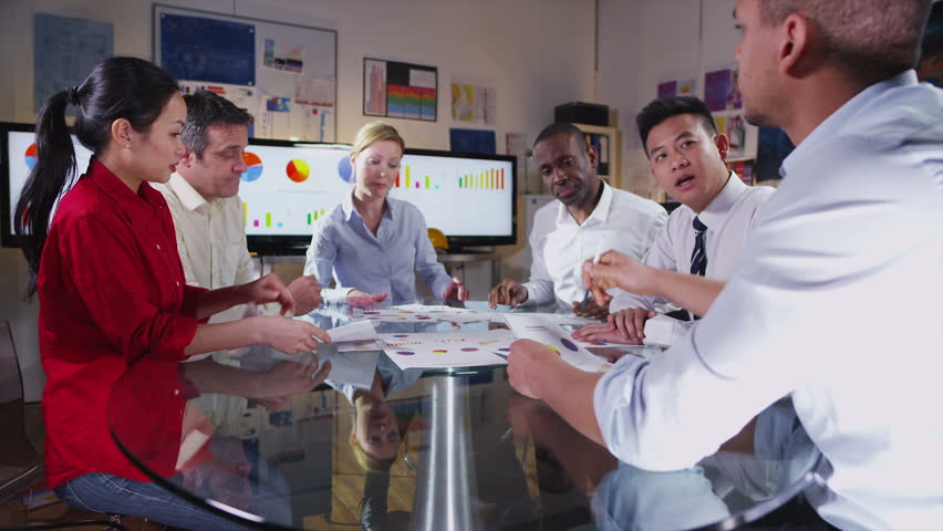 Time lapse of  a busy team of architects or engineers in a meeting. They are looking at printed business statistics, construction models and a map of the world.  | Shutterstock HD Video #5132747