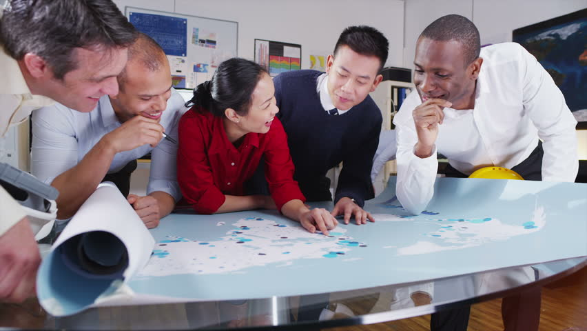 Happy and attractive mixed ethnicity team of architects or engineers of  are looking at a map of the world and discussing potential new sites for building development. In slow motion. | Shutterstock HD Video #5133443