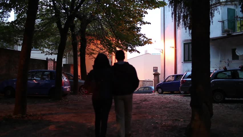 Video clip of man and woman walking on the street in the evening, shoulder to shoulder.