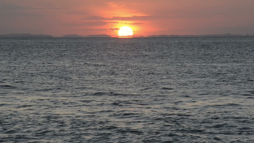 Sun setting as a ball of fire on the horizon over the ocean