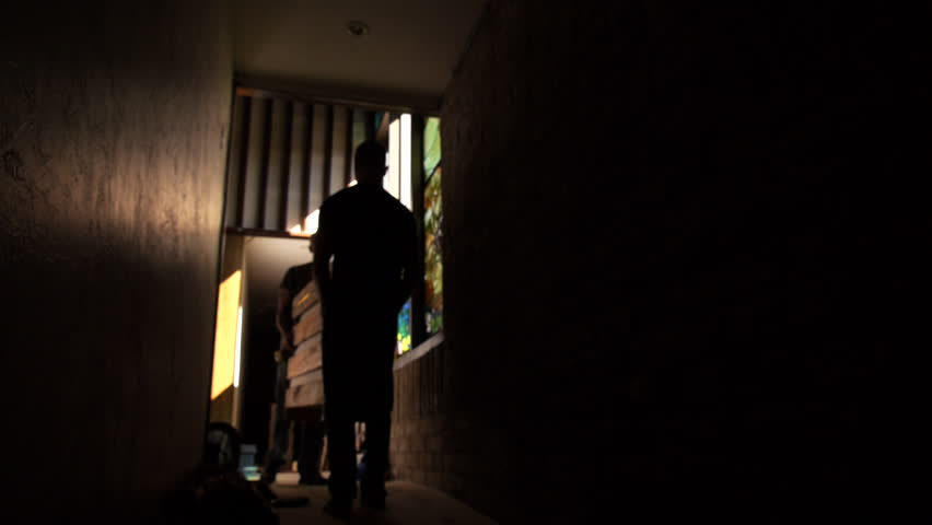 Men carry large wooden box down dimly lit corridor