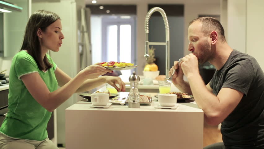 Young couple eating meal in the kitchen