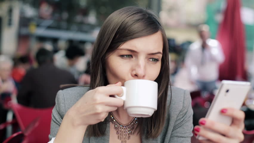 Businesswoman with smartphone drinking coffee in cafe
