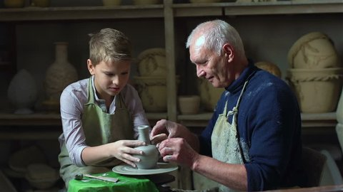 Elderly artisan sharing experience with his teen student