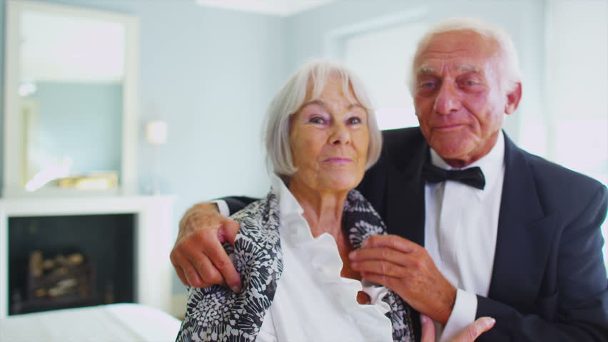 Attractive senior couple in formal evening wear share a kiss as they are getting dressed for an evening out. In slow motion.