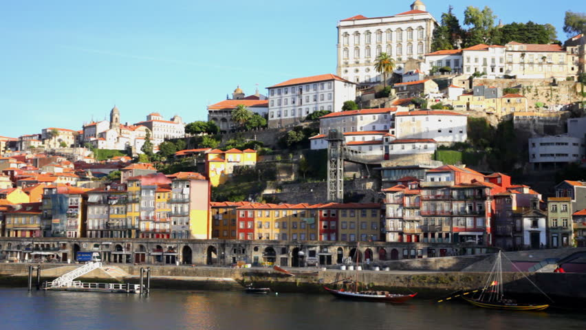 Panoramic view of shore with bright buildings and ships parked on bank, Portu, Portugal