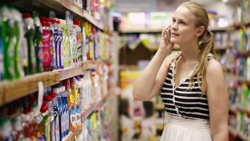 Woman with a long blond ponytail chatting on her mobile while out shopping standing in an aisle in the supermarket | Shutterstock HD Video #5250143