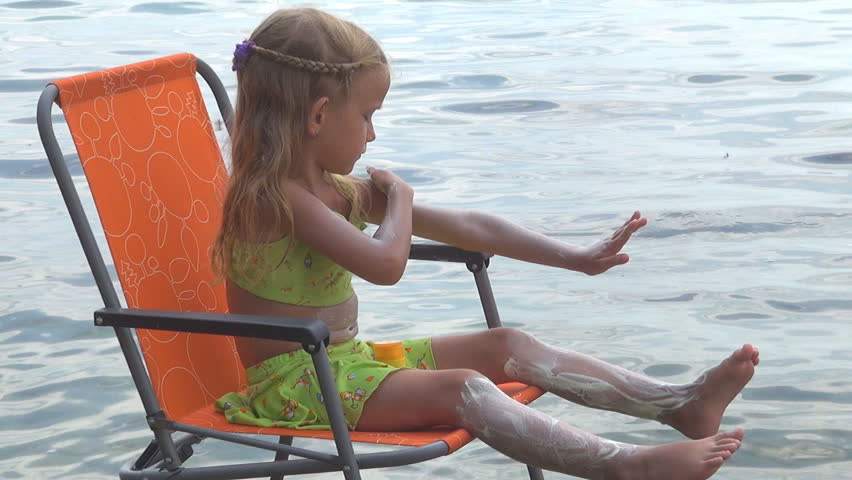 Little Girl Applying Sunscreen Lotion On A Beach Chair At Seaside, Child,  Kid Protecting