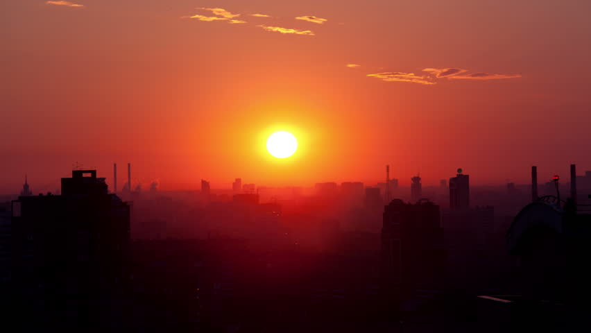 4K footage of Sunrise over the city. Time lapse. High angle. Aerial view. The roofs of the houses lit by soft warm light