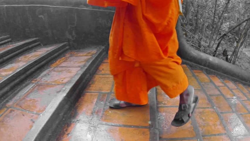 Monk climbing the stairs to a temple in Cambodia at slow motion under the rain