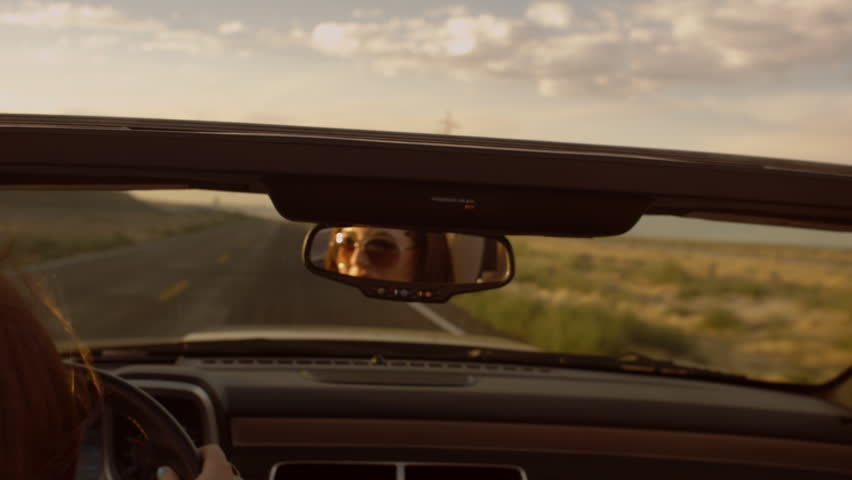 Model Driving A Convertible Through The Desert, Looking In The Rearview Mirror
