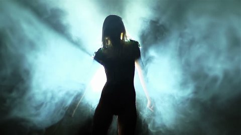 Backlit showgirl making a dramatic performance among smoke streams and beams o light