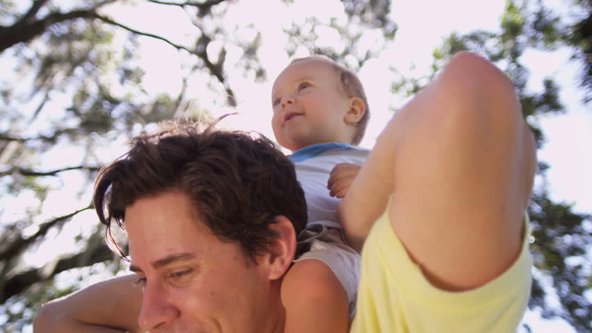 Portrait cute little male toddler laughing sitting on young fathers shoulders outing park sun lens flare head shoulders shot on RED EPIC, 4K, UHD, Ultra HD resolution