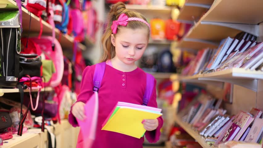 Little girl chooses the exercise-book in the department store with school supplies