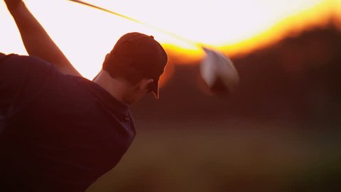 Close up male Caucasian golf professional practicing his swing on green before teeing off in silhouette sunset close up shot on RED EPIC, 4K, UHD, Ultra HD resolution