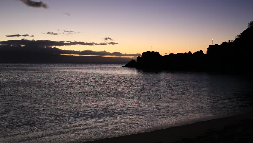 Sunset at Ka'anapali Beach or Black Rock with torches light on one of Maui Hawaii's best beaches.  Each night a cliff diver lights the torches and dives off the black rocks.