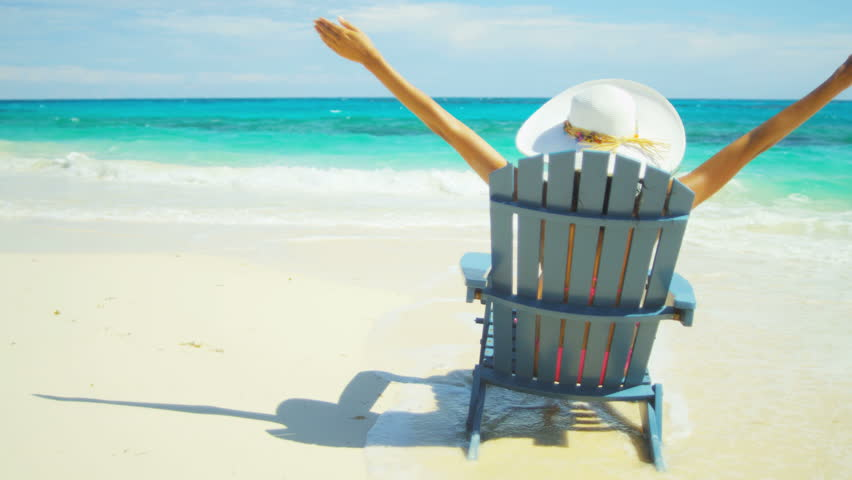 Girl in sun hat sitting wood beach chair celebrating achieving her luxury  island lifestyle shot on RED EPIC a2df54ff2a2