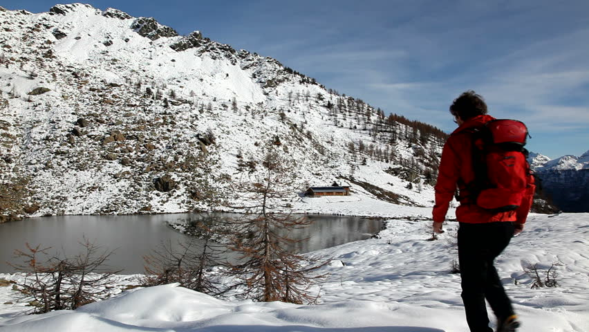 One young male hiker stands in front of a alpine lake looking to the snowy landscape, rear view. Red jacket, black pants. HD1080p Canon 5Dmk2 Buffet Lake, Champorcher, Val d'aosta, Italy, Europe.   Shutterstock HD Video #5364743