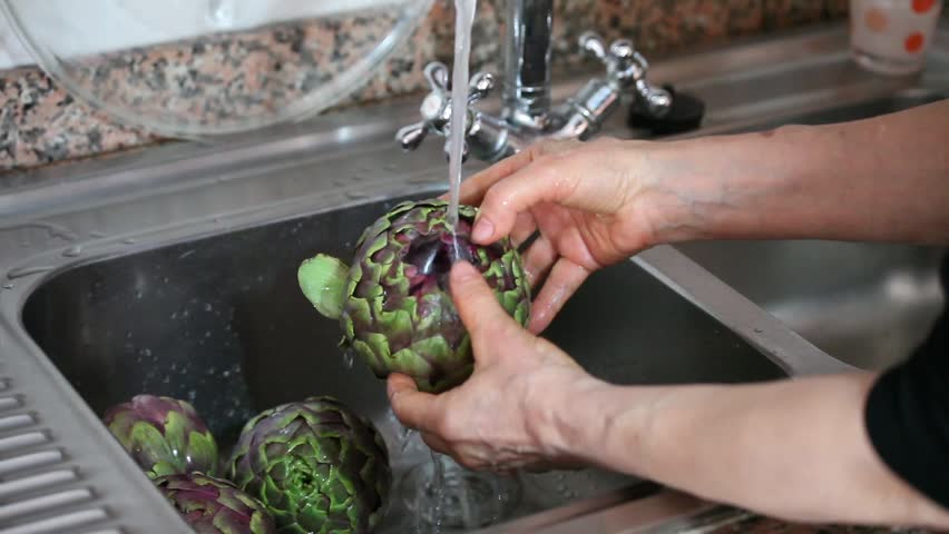 Video clip of woman cleaning artichokes.