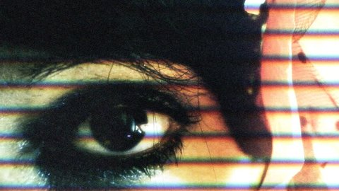 A woman's eyes as seen on an old analogue tv with noise, grain and scanlines. Macro shot.