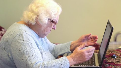 Old woman and computer. Forgotten password or other computer problems