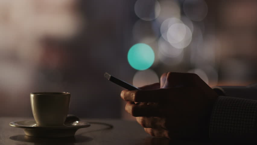 Man Typing a Message Using Mobile Phone at Evening Time in Coffee House.Close-Up. Shot on RED Digital Cinema Camera in 4K, ultra-high definition, UHD