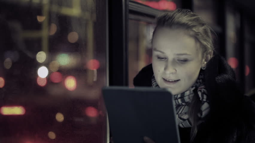 Young woman watching video on touchpad, then choosing another one during evening ride in the bus. Defocused city traffic in the bus window
