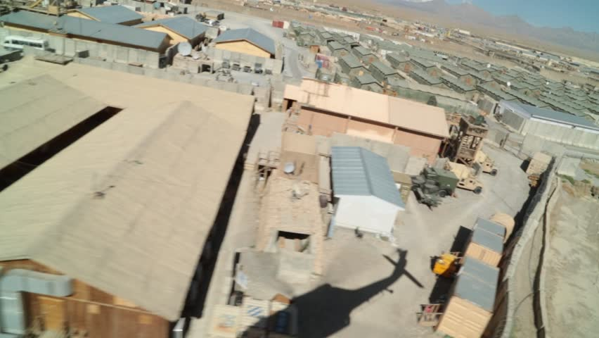 Shadow of helicopter rising above base in Afghanistan, aerial view pov