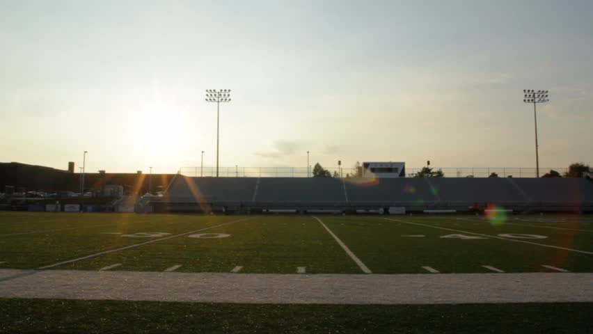 Pan of football stadium at sunset.