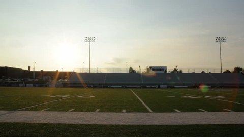 Pan of football stadium at sunset.