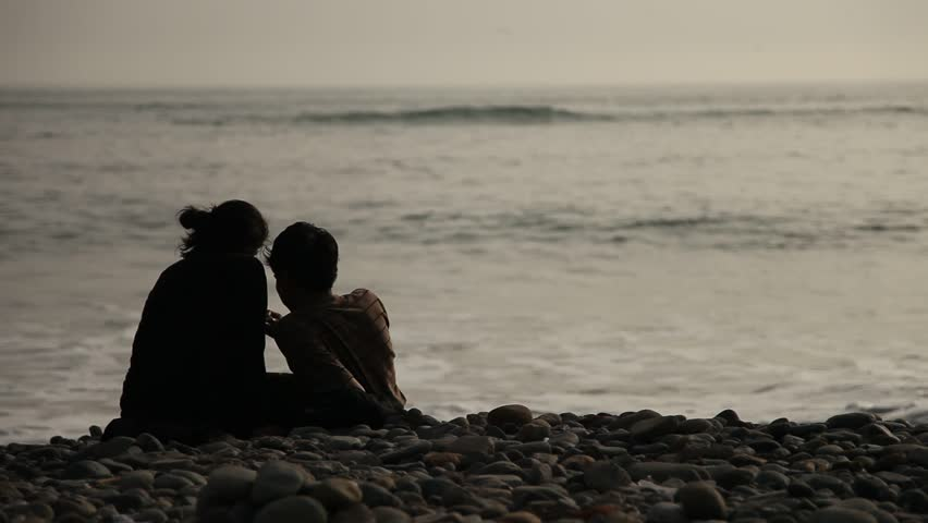 video footage of a couple at a beach silhouetted