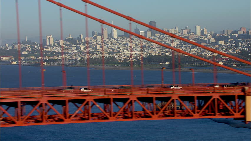 San Francisco City Bridge. The scene shows the city of San Francisco. The shot focuses on the downtown portion of the city. Traffic is shown moving on the Golden Gate Bridge.
