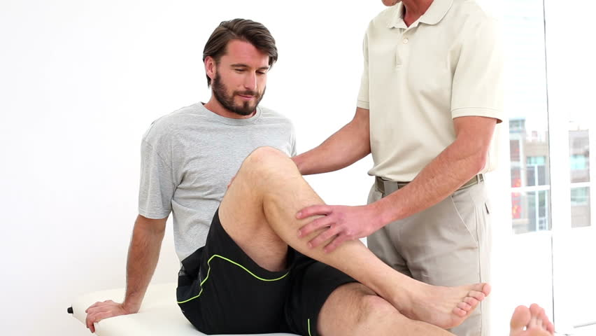 Physical therapist checking injured patients knee in his office at the hospital