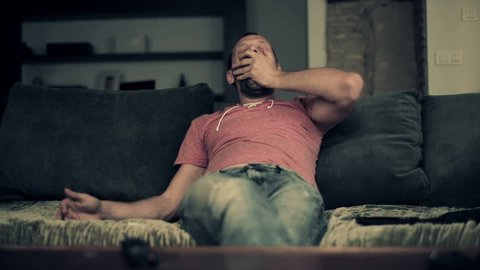Sleepy young man stretching and yawning on sofa at home