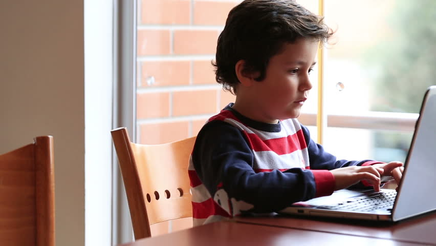 smart cute kid studying, using laptop at classroom