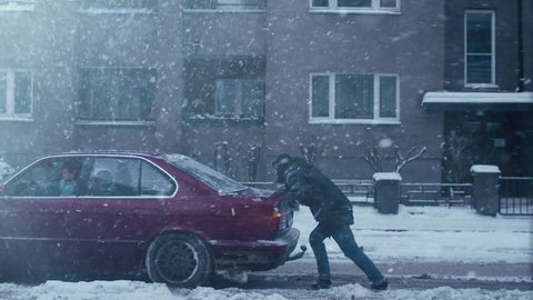 Man is pushing broken down car at winter time. Shot on RED Digital Cinema Camera in 4K (UHD), so you can easily crop, rotate and zoom, without losing quality.