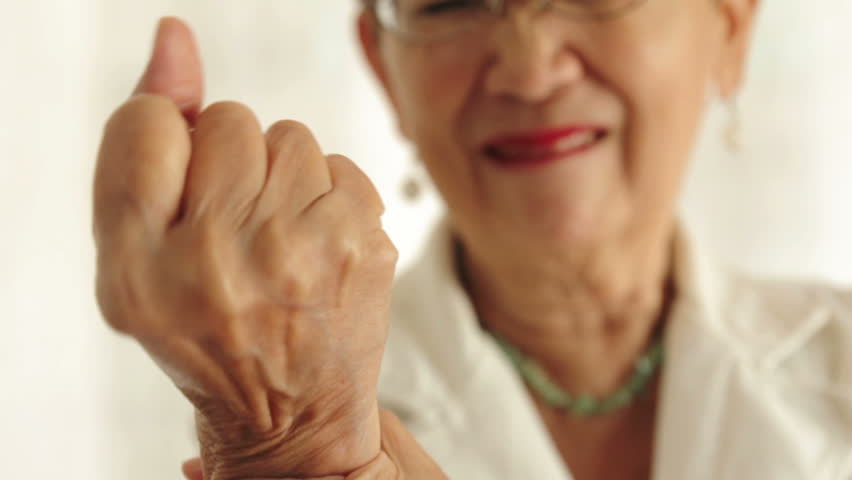 Elderly woman suffering from arthritis pain of the hand.
