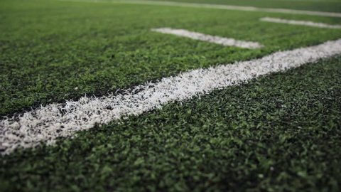 Close up of the out of bounds line on a turf football field.