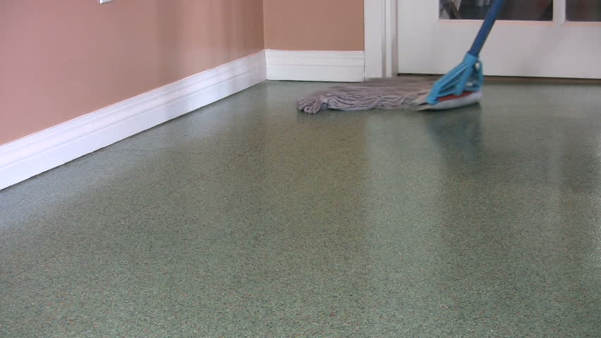 A housewife mops a green floor at her suburban home.