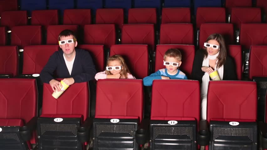 Family watching 3D movie through special glasses and eating popcorn at the cinema