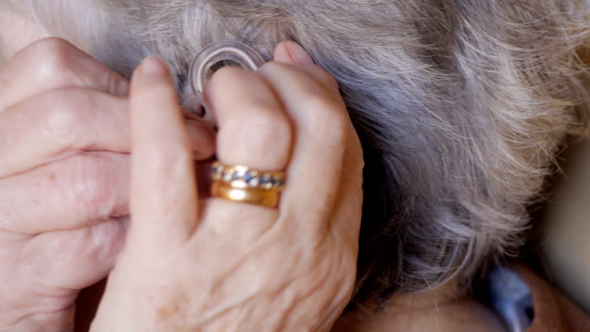 Elderly woman fitting hearing aid