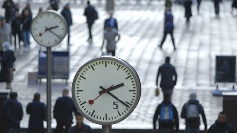 Commuters and Bankers walk past the Six Public Clocks on Reuters Plaza, Canary Wharf