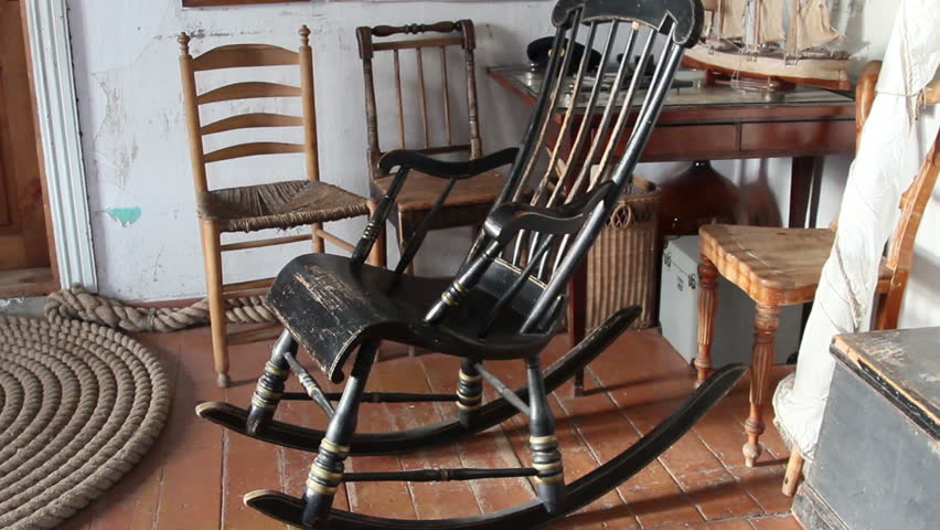 the black old rocking chair there are three chairs at the back and a small boat decor on the table stock footage video