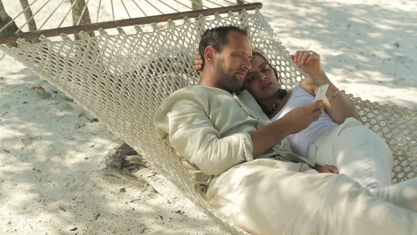 Couple with smartphone sitting on hammock on exotic beach