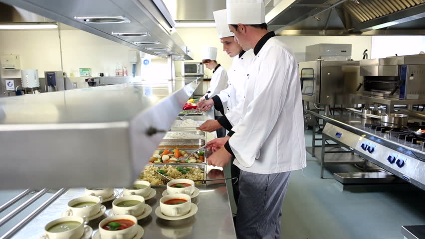 Busy Restaurant Kitchen waitress collects her order from the chef in a busy hotel or