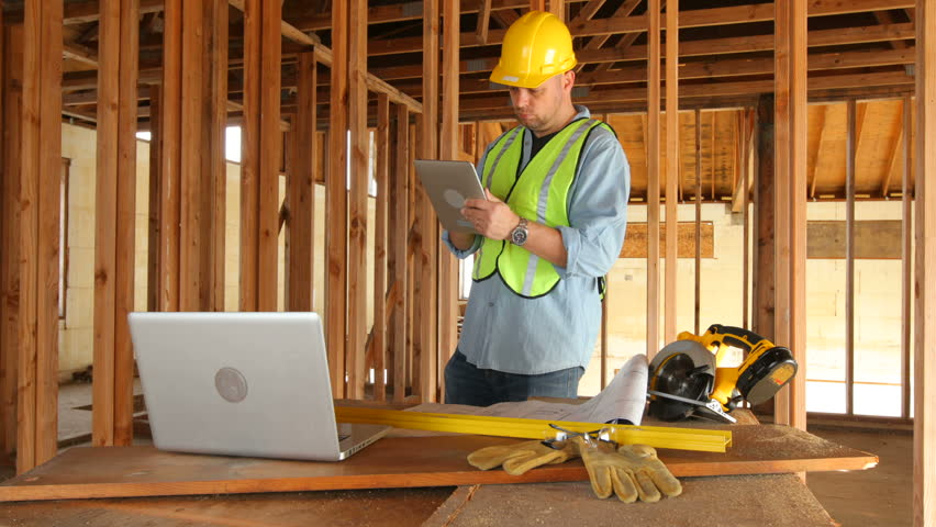 Construction worker using digital tablet on work site