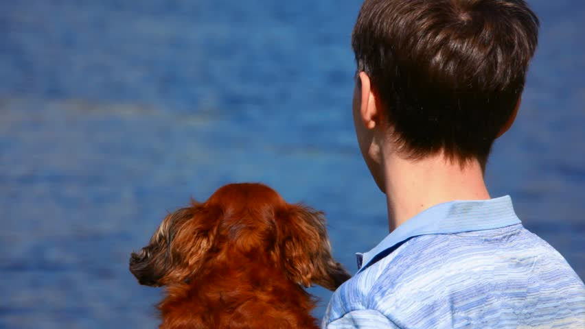 men with dog look at sea