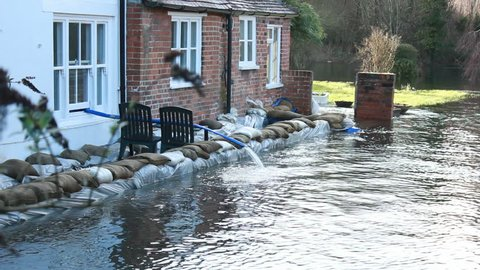 BRITAIN - CIRCA FEB 2014:Water pumped from flooded garden - February 2014 - Britain faced unparalleled natural disaster. Floods caused damage and transport chaos around the country.